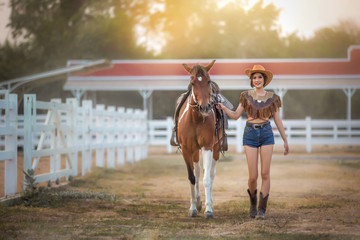 Beauty Asian cowgirl and her horse.