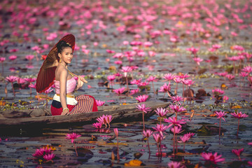 Asia women on the boat in the lotus pond. She wears Thai traditional dresses.