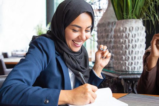 Happy businesswoman taking notes in coffee shop. Young Muslim business woman in hijab and office suit writing in notebook and laughing. Muslim business professional concept