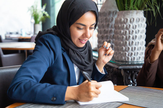 Confident businesswoman working on business plan in coffee shop. Young Muslim business woman in hijab and office suit writing notes in cafe. Work in cafe concept