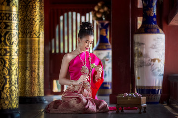 The woman wears a Thai dress, folds the lotus flower. To prepare to worship the Buddha In a wooden temple and Thai pattern.