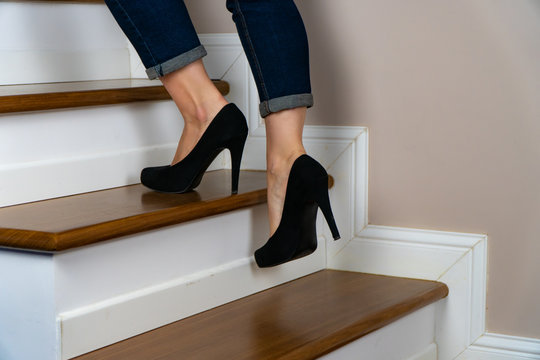 girl with heels and jeand on the stairs going up