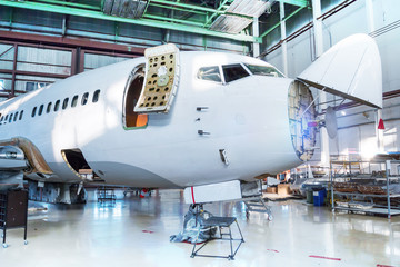 White passenger airplane under maintenance in the hangar. Checking mechanical systems for flight...