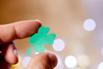 leaf of clover shape cut from paper in the hand
