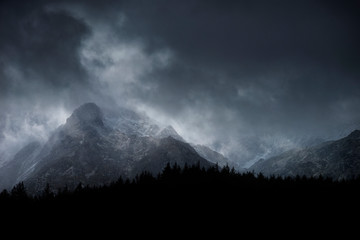 Wall Murals Gray Stunning moody dramatic Winter landscape image of snowcapped Y Garn mountain in Snowdonia