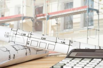 Baustelle für ein Haus, Taschenrechner und Baupläne
