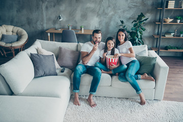 Fototapeta Portrait of nice attractive lovely cheerful friendly idyllic family wearing casual white t-shirts jeans denim sitting on sofa enjoying video holiday at industrial style interior living-room obraz