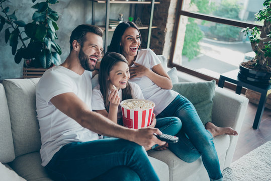 Portrait of nice attractive lovely positive glad cheerful cheery family wearing casual white t-shirts jeans denim sitting on divan having fun watching video switching channel spending free time
