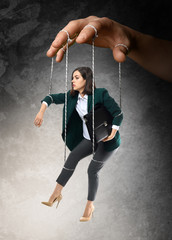 Hand of puppeteer manipulating woman as marionette on grey background