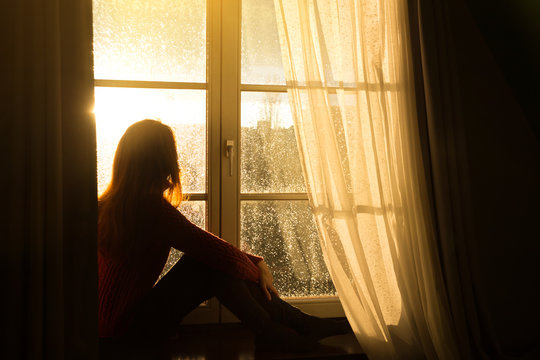 girl sitting on a windowsill and looking at the evening city
