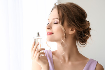 Beautiful young woman with bottle of perfume indoors