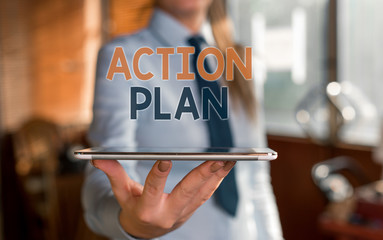 Writing note showing Action Plan. Business concept for detailed plan outlining actions needed to reach goals or vision Blurred woman in the background pointing with finger in empty space