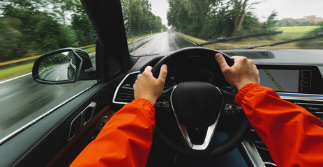 hands of car driver on steering wheel, Driving car at a rainy day on a country road,  road trip - POV, first person view shot