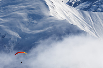 Fototapete - Paragliding at snowy mountains in haze