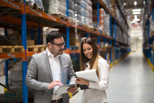 Warehouse management team checking organization and distribution in storage shipping center. Two beautiful elegant business people discussing about business improvement.