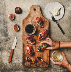 Party or catering food. Flat-lay of crostini with prosciutto, goat cheese and grilled figs on wooden board and female hands holding canape and glass of white wine over concrete background, top view