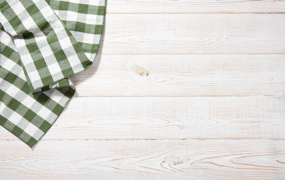 Kitchen towel on empty wooden table. Napkin close up top view mock up for design. Kitchen rustic background.