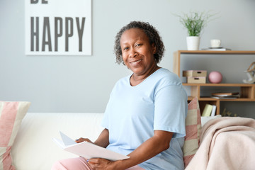Portrait of African-American woman reading book at home
