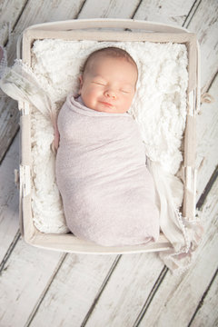 Smiling newborn baby girl sleeping in white basket on wood floor background