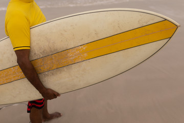 Senior male surfer with surfboard standing on the beach