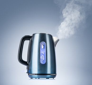 Boiling electric kettle gives off steam on blue background