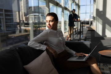 Caucasian businesswoman with laptop sitting on the sofa and looking away in office