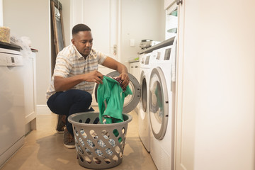 African American man washing clothes in washing machine