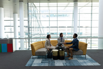 Multi-ethnic business people sitting and discussing with each other in lobby