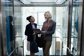Multi-ethnic businesswomen discussing over digital tablet in office elevator