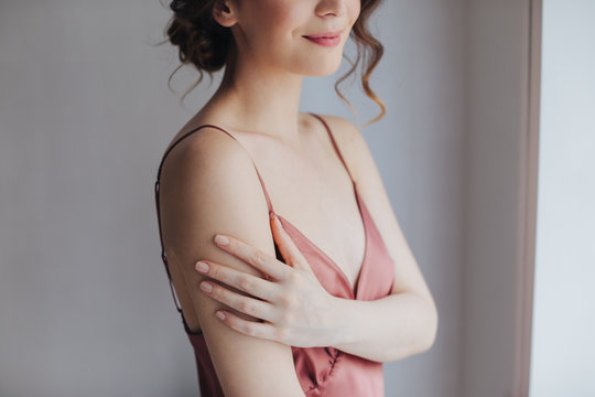 Portrait of cropped unrecognisable tender young woman in silky nightgown touching her shoulder.