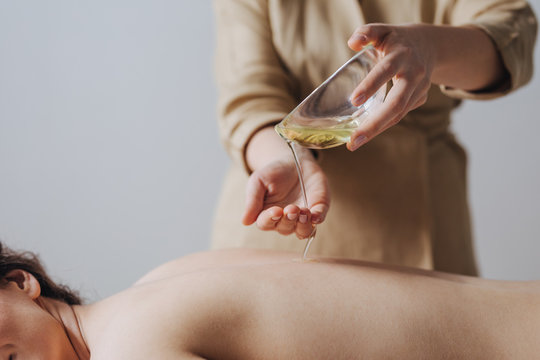 Hands of unrecognisable woman masseuse pouring massage oil on woman's back.
