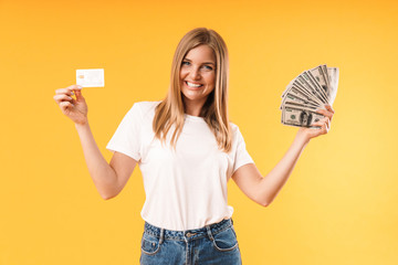 Image closeup of positive blond woman wearing casual t-shirt rejoicing while holding credit card and cash money