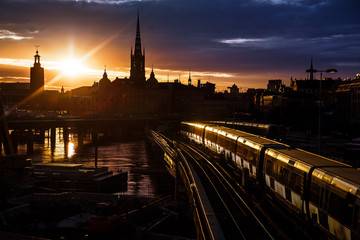 Fototapeten Stockholm Stockholm city skyline. The view of Old Town, Gamla Stan, and Riddarholmen Church from The Central Bridge Centralbron with local trains on it during sunset. Sweden.