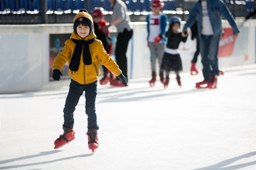 Happy boy with hat and jacket, skating during the day, having fun .