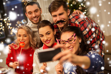 holidays and celebration concept - happy friends with party props taking selfie by smartphone at...