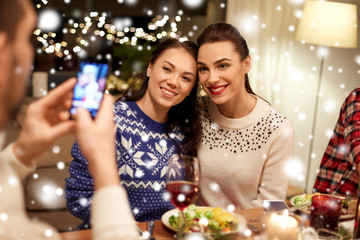 holidays and celebration concept - happy friends having christmas dinner at home and taking picture by smartphone over snow