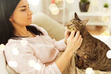 Fototapete - pets, hygge and people concept - close up of woman with tabby cat in bed at home