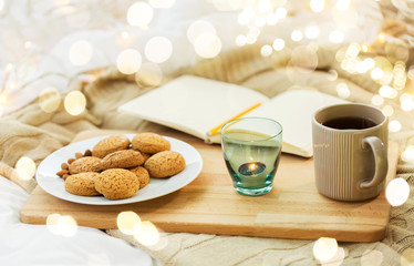 Fototapete - food, hygge and comfort concept - oatmeal cookies, tea, diary and candle in holder at home