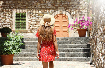 Curious young woman with red dress and hat walking in street in Taormina, Italy. Rear view of happy cheerful girl visiting Sicily Island.