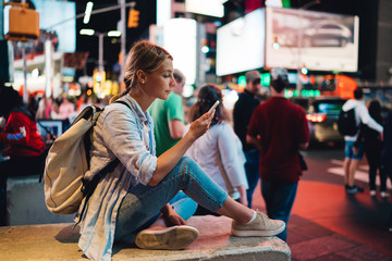 Young woman reading message on mobile phone using internet in roaming during trip to New York, female traveler posting pictures in blog via smartphone sitting at crowded Times square in evening