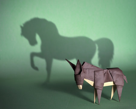 Concept of hidden potential. A paper figure of a donkey  that fills the shadow of a mustang. 3D illustration