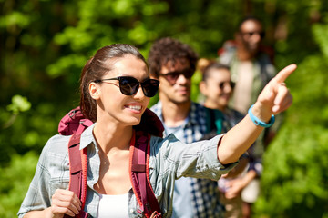 travel, tourism, hike and people concept - woman showing something to group of friends walking with backpacks in forest