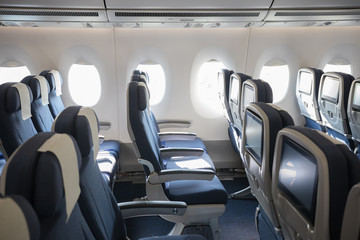 An economy class empty cabin of the airplane - empty blue chairs - monitors on the back of the chairs Fototapete