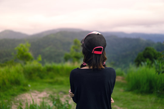 asian girl ware the cap and looking Mountain Multiple layers in the top of the hill