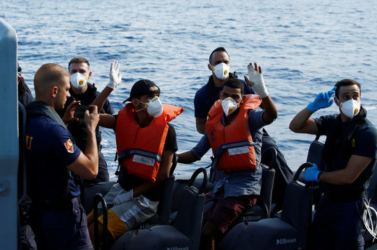 Two Tunisian migrants being medically evacuated to Malta by the Armed Forces of Malta wave to colleagues and crew on the German NGO Sea-Eye migrant rescue ship 'Alan Kurdi' in international waters off Malta in the central Mediterranean Sea