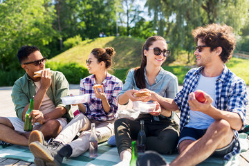 leisure and people concept - group of happy friends having picnic and eating sandwiches at summer...