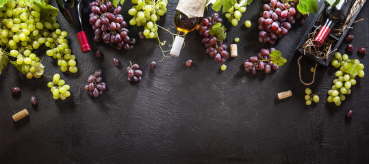 Red And White Grapes With Bottles On A Black Background. Top View