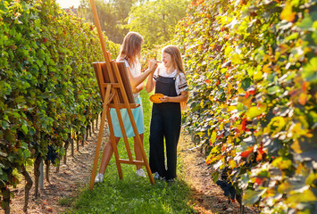 Two playful young talented preteen girls painting picture on easel having fun outdoors in vineyard at warm autumn sunny day. Summer lifestyle. Creative hobby and leisure activity.