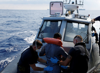 An injured Tunisian migrant is assisted by Armed Forces of Malta sailors during his medical evacuation to Malta from the German NGO Sea-Eye migrant rescue ship 'Alan Kurdi' in international waters off Malta in the central Mediterranean Sea
