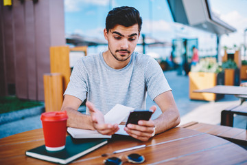 Skeptical male blogger amazed with incoming notification with strange message about interner changes in tariff plan on smartphone device sitting outdoors at wooden desktop with books and coffee to go